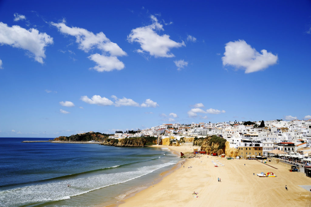 The sun beams down from a blue sky on the beach in Albufeira.